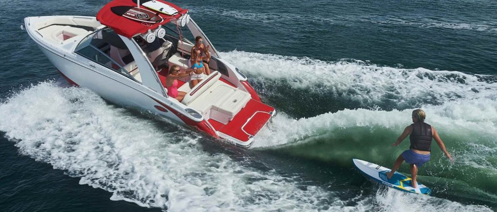 Man wakesurfing behind a red and white boat